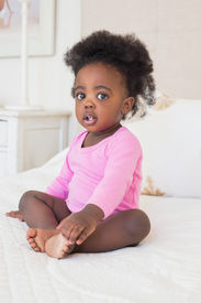 stock photo of babygro  - Baby girl in pink babygro sitting on bed at home in the bedroom - JPG