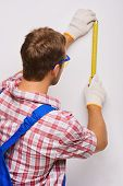 Young repairman with measure tape