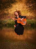 Young Woman Jumping With Guitar