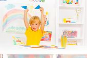 Blond cute boy learning shapes holding triangles