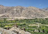 Ancient Castle And Green Village View Among Desert Mountains
