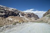 stock photo of ravines  - Gravel Mountain Road In Ravine of Indian Himalayas - JPG