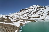 Torquoise Lake In High Altitude Mountains With Ice Cakes