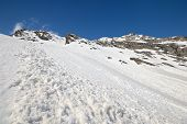 stock photo of avalanche  - Spring avalanche fans caused by heat and snowdrift on the ridges at high altitude - JPG