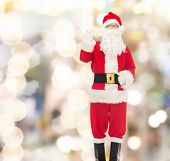 christmas, holidays, gesture and people concept - man in costume of santa claus pointing finger up over lights background