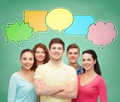 school, education, communication and people concept - group of smiling teenagers over green board background with text bubbles