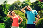 fitness, sport, training and lifestyle concept - smiling couple stretching outdoors