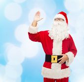 christmas, holidays, gesture and people concept - man in costume of santa claus waving hand over blue lights background