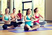 sport, meditation and lifestyle concept - smiling women meditating on mat in gym