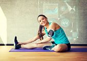 fitness, sport, training, future technology and lifestyle concept - smiling woman stretching leg on mat in gym over graph projection