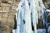 Man climbing frozen waterfall.