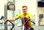 sport, fitness, lifestyle and people concept - smiling man exercising in gym