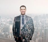 business, people, development and future concept - smiling young buisnessman over transparent city background
