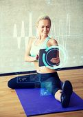 fitness, technology, future technology and sport concept - smiling woman with tablet pc sitting on in gym over cardiogram projection
