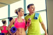 sport, fitness, lifestyle and people concept - smiling couple with water bottles in gym