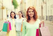tourism, travel, vacation, shopping and friendship concept - smiling teenage girls with shopping bags on street
