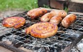 Tasty Sausages Cooking Over The Hot Coals On A Barbecue Fire