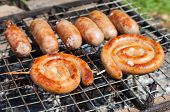 Tasty Pork And Beef Sausages Cooking Over The Hot Coals On A Barbecue Fire