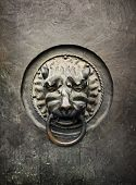 Antique Door Knocker In The Form Of A Lion's Head On Old Metal Door