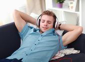 Man listening music in headphone on the sofa at home