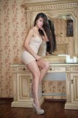 pic of nearly nude  - Charming young brunette woman in tight fit short nude dress in front of a mirror - JPG