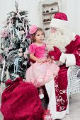 little girl in a beautiful pink dress sits on a lap at Saint Nicolas