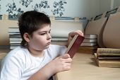 Teenager Boy Reading A Book In Room