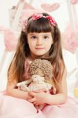 Little girl with plush toy in his hands.