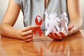 Female hands holding paper people and a red hiv ribbon, closeup