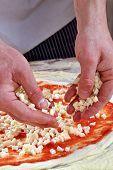 Preparing margarita pizza, adding mozzarella cheese.
