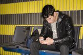 Young Man Typing On Smartphone Waiting For Subway Train