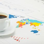 Cup Of Coffee Over World Map And Financial Documents - Studio Shot