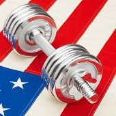 Metal Dumbbells Over Us Flag As Symbol Of Healthy Nation - Studio Shot