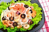 Rice Noodles With Seafood, Olives And Green Salad On Black Plate