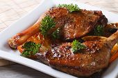 Roasted Duck Legs On A White Plate Close Up. Horizontal