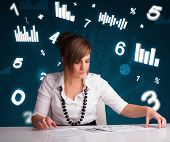 Pretty young businesswoman sitting at desk with diagrams and statistics