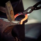 foto of horseshoe  - Making decorative element in the smithy on the anvil - JPG