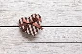 Heart shaped Valentines Day gift box on white wood. Holiday background.