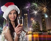 Young Santa girl with champagne glass in city at night. Celebration theme.