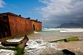 foto of shipwreck  - Rusted decaying shipwreck on beach with crashing waves - JPG