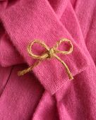 Twine bow on vivid pink cashmere robe.