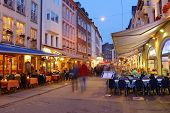 DUSSELDORF, GERMANY - JUNE 29, 2013: People walking and resting on the Market street in evening. The street now is the favorite pedestrian zone for tourists and locals. Motion blur