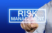 picture of risk  - Business concept image of a businessman clicking Risk Management button on virtual screen over blue background - JPG