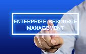 foto of enterprise  - Business concept image of a businessman clicking Enterprise Resource Management button on virtual screen over blue background - JPG