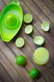 stock photo of lime  - green limes with lime juice in the glass on the table - JPG