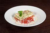 pic of lasagna  - Portion of lasagna garnished with salad greens - JPG
