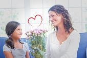picture of couch  - Heart against happy mother and daughter sitting on the couch with flowers - JPG