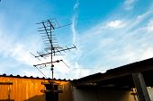 image of antenna  - Old TV antenna on the roof and blue sky white cloud background - JPG