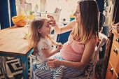 image of baby bump  - loving pregnant mother and her baby daughter playing at home in the kitchen - JPG