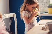image of pyjama  - cute toddler girl drinking tea for breakfast at home - JPG